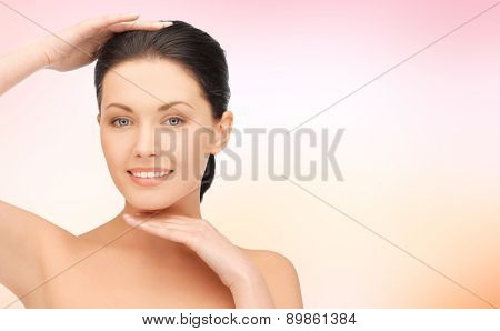 beauty, people and health concept - beautiful young woman touching her face and chin over pink background