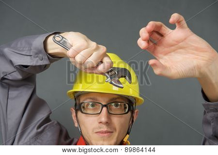 Young worker in helmet with wrench