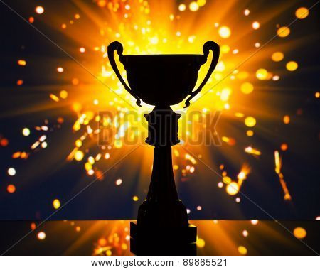 cup trophy silhouette against shiny sparks background