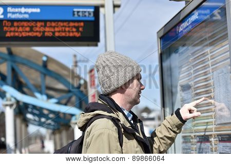 Passenger looking at timetable on a Russian commuter train station
