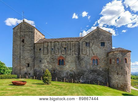 Medieval castle on green lawn under blue sky in Piedmont, Northern Italy.