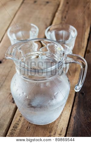 Glass Pitcher Of Water And Glass On Wooden Table.