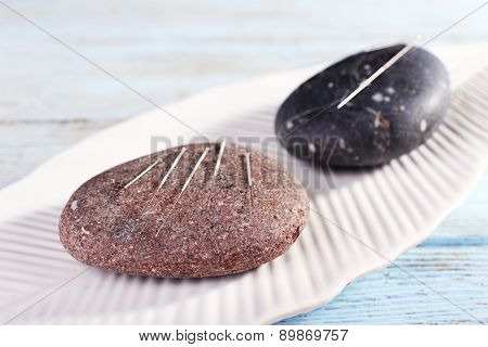 Acupuncture needles on plate with spa stones on wooden table, closeup