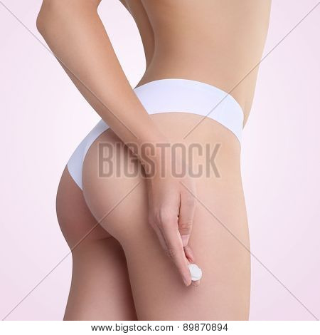 Female Applying Cosmetic Cream From Cellulite On The Buttocks