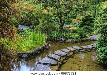 Decorative private garden on Vancouver Island in Canada - Butchart Gardens. The track of stones in  water in Japanese part of garden