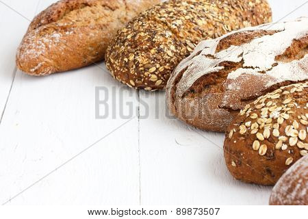 Variety of whole grain breads on white wood.