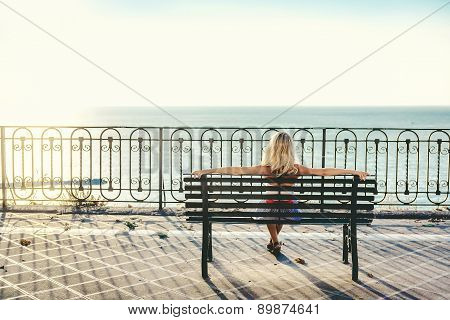 Blonde Woman Sitting On A Bench And Looking At Sea