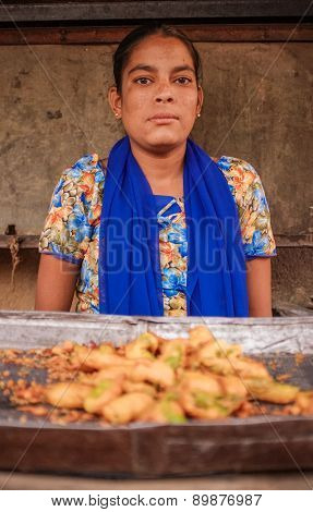 KAMALAPURAM, INDIA - 02 FEBRUARY 2015: Young Indian woman in dress and wearing scarf selling fried vegetables on a market close ot Hampi