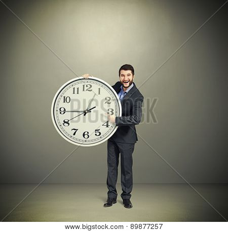 laughing successful businessman in formal wear pointing at clock dial and looking at camera over dark grey background