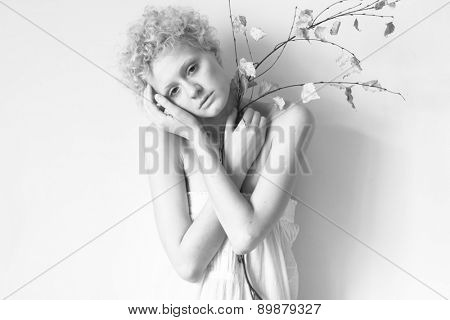 Young tender girl with a dry branch in his hand. Black and white photography in bright colors.