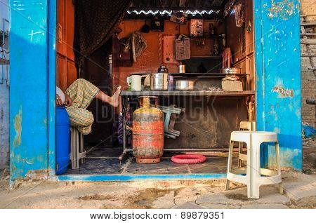 KAMALAPURAM, INDIA - 02 FEBRUARY 2015: Indian vendor sitting in his chai shop showing only legs.