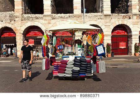 Seat Cushions Are Sold In Front Of The Famous Old Roman Arena Of Verona