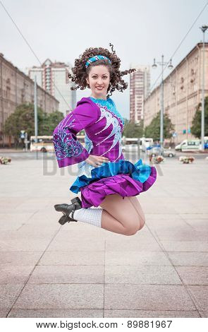 Young Beautiful Girl In Irish Dance Dress And Wig Jumping