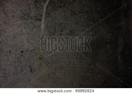 Dark concrete wall with scratches and wear.