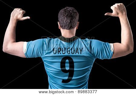 Uruguayan soccer player on black background