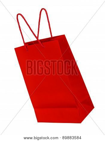 Bright Red Shopping Bag Falling Through The Air On An Isolated White Background