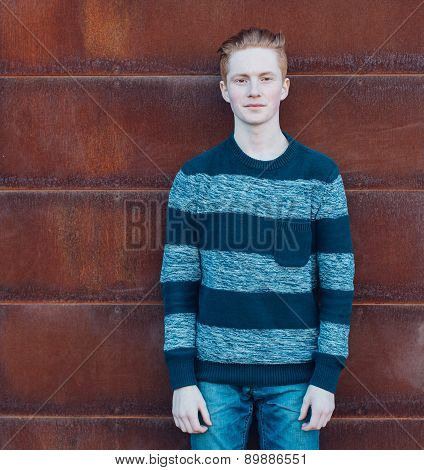 Young redhead man in a sweater and jeans standing next to metal rusty wall and smiling