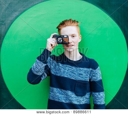 Young redhead man in a sweater and jeans standing next to green wall and taking photos vintage camer