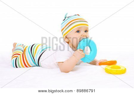 Colorful Baby Is Lying On The Floor And Bites Toy
