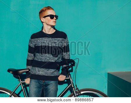young redhead man standing next to a vintage bicycle in suglasses near turquoise wall warm summer su