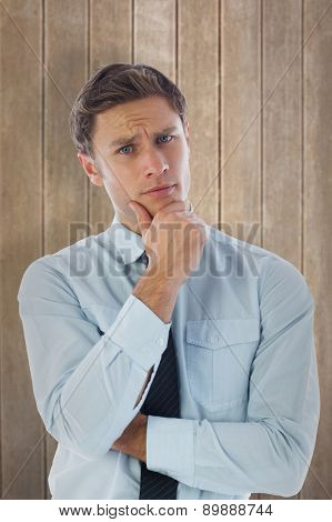 Thinking businessman with hand on chin against wooden surface with planks