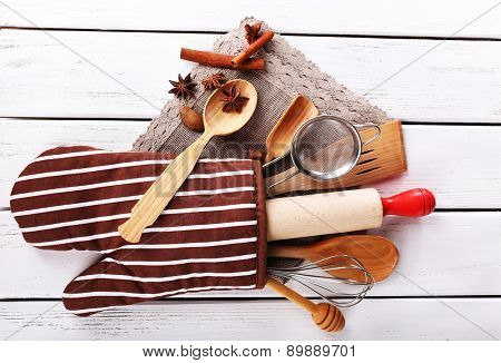 Set of kitchen utensils with cinnamon sticks and star anise in mitten on wooden background