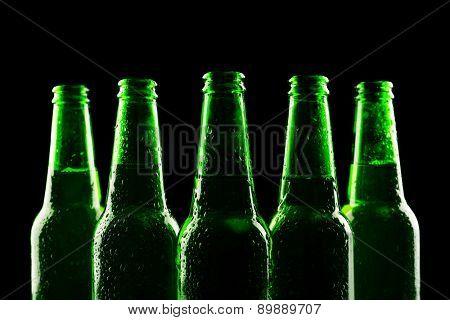glass bottles of beer on dark background