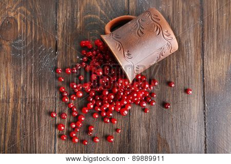 Red cranberries with cup on wooden table, top view
