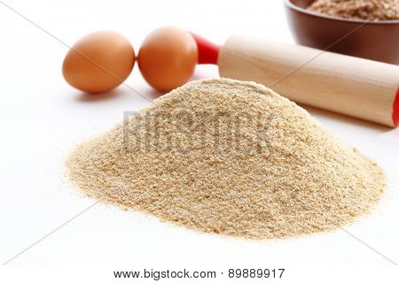 Heap of meal with eggs and plunger isolated on white