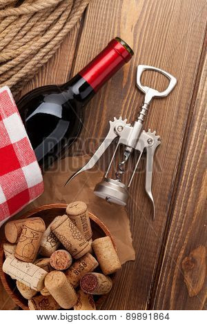 Red wine bottle, bowl with corks and corkscrew. View from above over rustic wooden table background