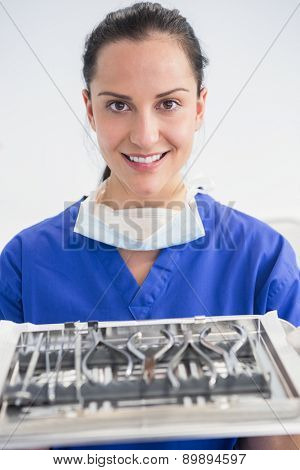 Smiling dentist holding tray with equipment in dental clinic