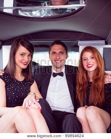 Pretty girls with ladies man in the limousine on a night out