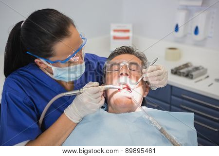 Dentist examining a patient with tools and light in dental clinic
