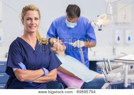 Portrait of a smiling nurse her arms crossed and dentist with the patient behind him
