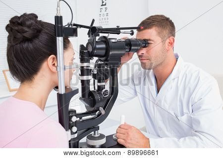 Male optician examining female patients eyes through slit lamp in clinic