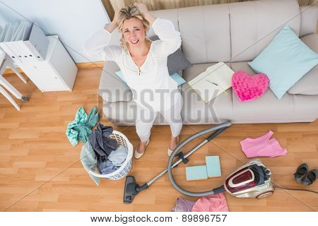 Angry woman in a chaotic living room with vacuum cleaner at home