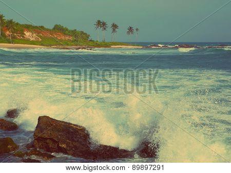 Large ocean waves breaking on the rocks of tropical coast - vintage retro style