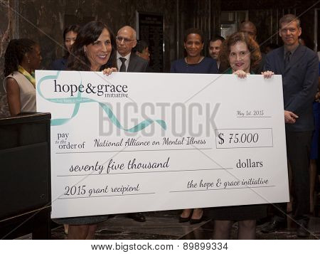 NEW YORK - MAY 5, 2015: 'hope & grace initiative' board member and CMO of Coty Skincare Jill Scalamandre presents Exec Dir of NAMI, Mary Giliberti a check at the ceremony in the Empire State Building.