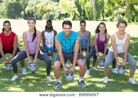 Fitness group squatting in park with kettle bells on a sunny day