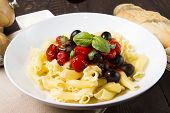 stock photo of olive shaped  - a close up image of cooked Italian pasta with tomate and olives - JPG