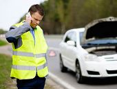 stock photo of towing  - Man calling car towing service on a highway roadside  - JPG