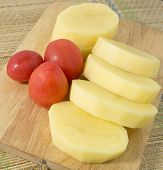 stock photo of batata  - Vegetable Slice Potatoes and Fresh Tomatoes on A Wooden Cutting Board - JPG