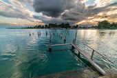 stock photo of jetties  - Old and damaged wooden jetty on lake Poso in central Sulawesi Indonesia with dramatic cloudscape at the horizon at sunset - JPG