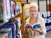 pic of book-shelf  - Elderly lady standing next to book shelves in library - JPG