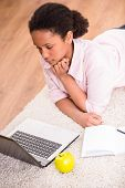 pic of mulatto  - Young pretty mulatto schoolgirl laying on the carpet and using laptop - JPG