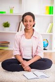 image of mulatto  - Young pretty mulatto schoolgirl sitting on the carpet on colorful background - JPG