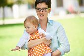 picture of mother baby nature  - portrait of happy mom and baby daughter smiling at park nature - JPG