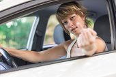 stock photo of middle finger  - Attractive blond young woman driving a car and showing the middle finger - JPG