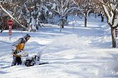 stock photo of blowers  - A thick layer of snow covers the road as a man with a snow blower tries to find his walkway to clear - JPG