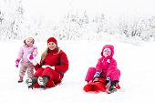 stock photo of toboggan  - mother and her little daughters with bobs in snow - JPG